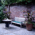 Courtyard with brick walls, a bench and fountain