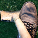 Foot pressing down on shovel in grass
