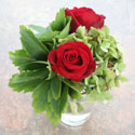 Red roses in vase with greenery