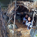 Two girls in a sticks and pine needles hideout