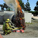 Fireman setting Christmas tree on fire for test