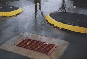 water with oil flowing into storm drain