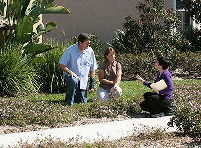 Woman talking to a couple while all are crouching down in a landscaped yard
