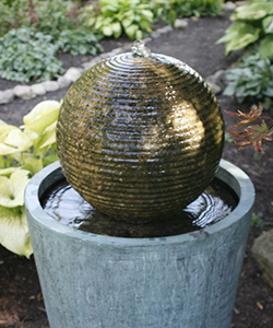 A fountain with a concrete sphere with water spilling over it into a pedestal