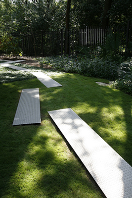 A lawn path made of long rectangles of diamond patterned sheet metal laid out in an irregular path