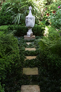 A green and shady path leading to a solemn urn