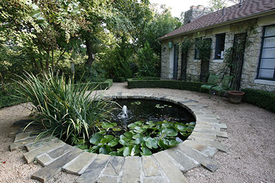 A round water garden with fountain in the middle of a garden