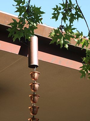 copper rain chain with bell-like attachments hanging from a gutter