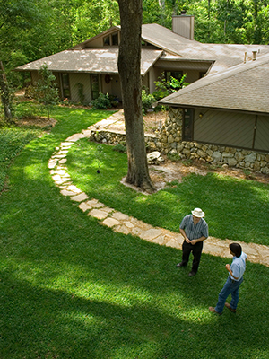 An ariel look down on two men talking on a shady, deep green home lawn