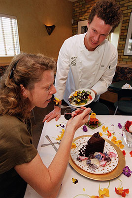 Man serving woman cake decorated with flowers