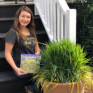 Woman sitting on front steps with her book and a potted rice plant