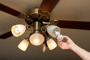 Hand putting new compact flurescent bulb in ceiling fan light fixture