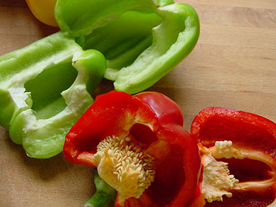 Green and red bell pepper on counter