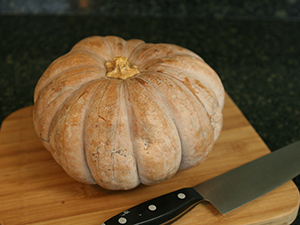 Orange-tan pumkin on cutting board with a large carving knife