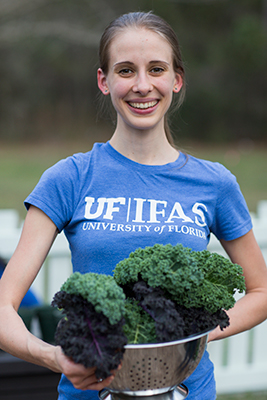 Woman wearing UF/IFAS shirt and holding freshly harvested kale