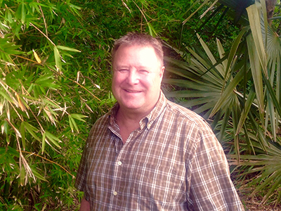 Photo of Terry Wawrzyniak in front of saw palmettos and bamboo plants