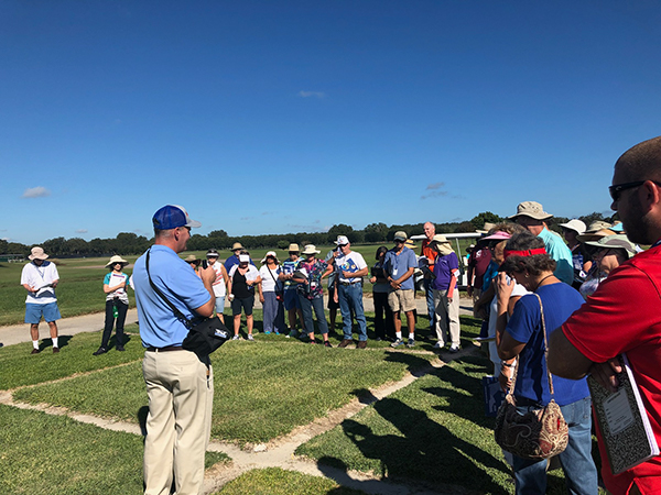 Man speaking to group out in a turfgrass field with squares of turf under foot and a bright blue sky overhead