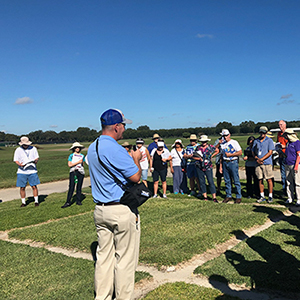 Man speaking to a group of people in a field of turfgrass plots under a very blue sky