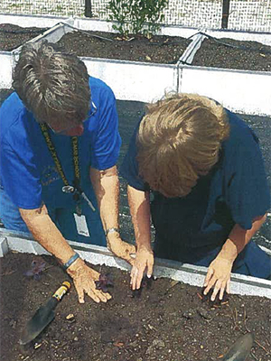 Student preparing soil for planting with assistance from a adult