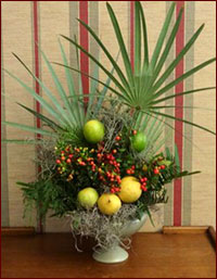 Natural holiday arrangement with citrus and palm fronds