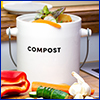 White container with the word compost on it, sitting on a cutting board with color vegetables