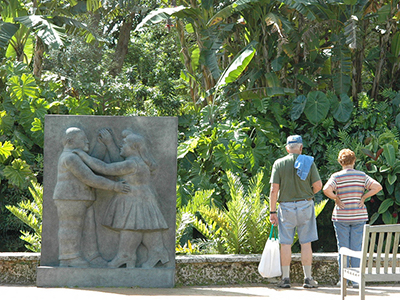 Vistors looking at the tropical plants next to relief-style statue of a couple dancing