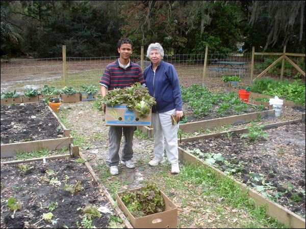 A young volunteer and a Master Gardener hold a box of produce in the garden.