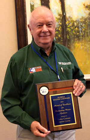 Luke Connor with his plaque for Outstanding Master Gardener of 2015