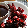 Deep red roselle fruits next to a cup of red tea