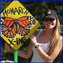 Samm Epstein next to a handpainted sign reading Monarch Crossing