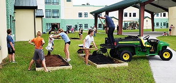 School children work on raised garden beds while man disperses compost