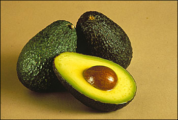 Avocados, one cut open so that seed is visible